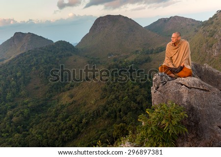 CHIANG DAO, THAILAND, JANUARY 05, 2015 : A Buddhist monk master is meditating at the top of the Chiang Dao mount at dusk for the new year in Thailand. - stock photo