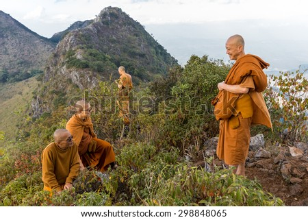 CHIANG DAO, THAILAND, JANUARY 05, 2015 : A group of Buddhist monks is standing at the top of the Chiang Dao mount at dusk for the new year in Thailand. - stock photo