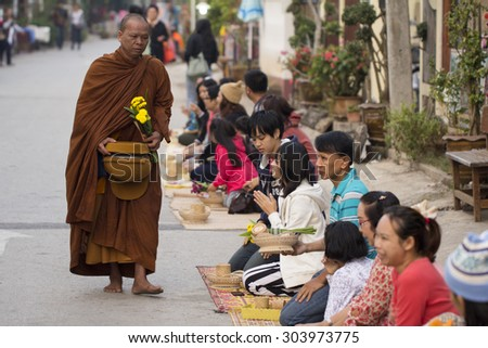 CHIANG KHAN, THAILAND - December 10, 2013 : Unidentified tourists offering sticky rice to Buddhist monk and Buddhist novice in the morning on December 10, 2013 at Chiang Khan, Loei, Thailand. - stock photo