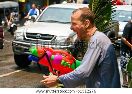 CHIANG MAI, THAILAND - APRIL 13: A guy aims water gun on April 13, 2010 in Chiang Mai, Thailand. Celebration of Thai New Year (Songkran water festival)  in 2010.