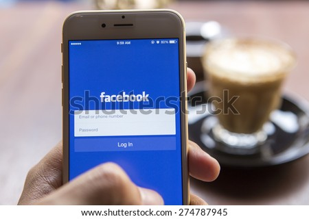 CHIANG MAI, THAILAND - APRIL 22, 2015: A man trying to log in Facebook application using Apple iPhone 6. Facebook is largest and most popular social networking site in the world. - stock photo