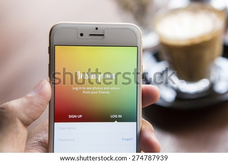 CHIANG MAI, THAILAND - APRIL 22, 2015: A man trying to log in Instagram application using Apple iPhone 6. Instagram is largest and most popular photograph social networking site in the world. - stock photo