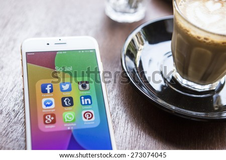 CHIANG MAI, THAILAND - APRIL 22, 2015: All of popular social media icons on smartphone device screen Apple iPhone 6 on coffee table. - stock photo