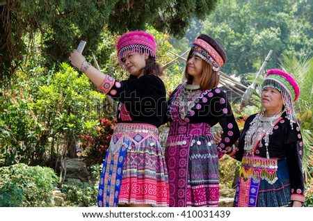 CHIANG MAI, THAILAND-APRIL 23,2016: girl mong doipui hill tribe is playing smart phone in garden, thailand - stock photo