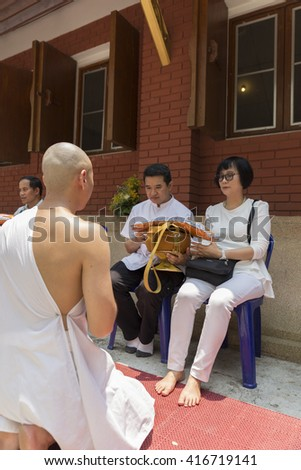 Chiang Mai, Thailand - April 30, 2016: man receive monk robe from their parent in buddhist monk ordination ceremony at Umong temple in Chiang Mai, Thailand on April 30, 2016.