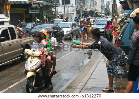 CHIANG MAI, THAILAND - APRIL 13: Thai guy throws water to girls on a bike on April 13, 2010 in Chiang Mai, Thailand. Celebration of Thai New Year (Songkran water festival)  in 2010.