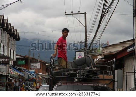 CHIANG MAI, THAILAND - AUGUST 30: A local worker standing in the back of a truck in the main street of Pai a small country town outside of Chiang Mai, Thailand on the 30th August, 2014.