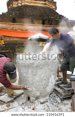 CHIANG MAI  THAILAND - AUGUST 12 : Buddhist metal cast ceremony for buddha statue , Coating outside mold before pour molten metal in mold  . Aug 12,2012 in Lok Molee Temple, Chiangmai, Thailand. - stock photo