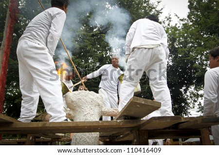 CHIANG MAI  THAILAND - AUGUST 12 : Buddhist metal cast ceremony for buddha statue , Pouring molten metal in mold  . Aug 12,2012 in Lok Molee Temple, Chiangmai, Thailand. - stock photo