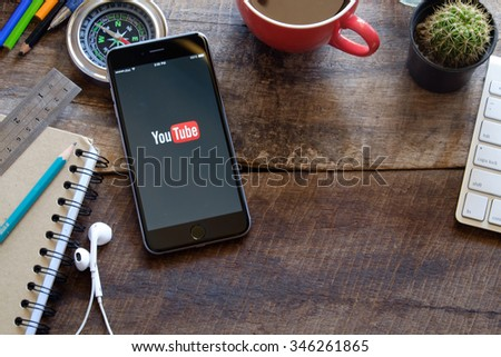 CHIANG MAI,THAILAND, DEC 02 2015 : Brand new Apple iPhone 6 plus with YouTube app on the screen lying on old wood desk with headphones. YouTube is the popular online video sharing website - stock photo