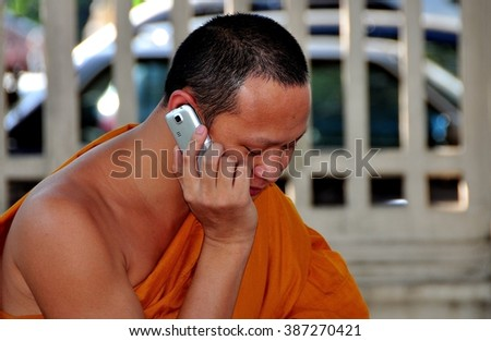 Chiang Mai, Thailand - December 21, 2012:  An orange robed monk sitting in a city square using his cellphone