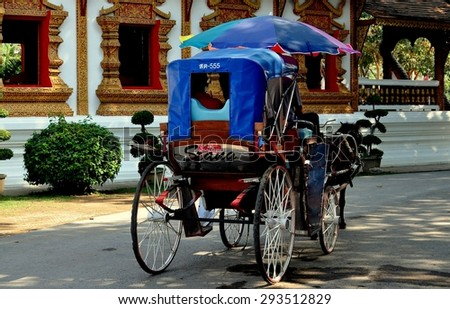 Chiang Mai, Thailand - December 30, 2012:  Horse-drawn carriage offers visitors a guided tour through King Mengrai's Wiang Kum Kam Ancient Village
