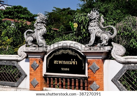 Chiang Mai, Thailand - December 31, 2012:  Two mythical stone dragons decorate a small roadway bridge over a klong (canal)