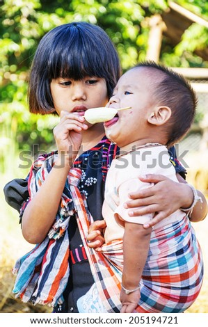 CHIANG MAI,THAILAND-DECEMBER 8 : Unidentified Red Lahu hilltribe kid sister fed ice cream her brother at Baan Huay Kub Kab, Kue Chang, MaeTang on December 8,2012 in Chiang mai,Thailand.