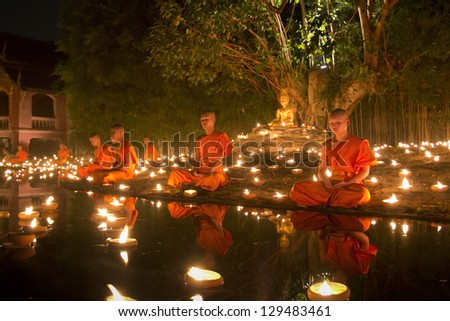 CHIANG MAI THAILAND - FEBRUARY 25 : Magha Puja Day is an important Buddhist festival celebrated in asian, Buddhist monk fire candles to the Buddha. Feb 25,2013 in Phan Tao Temple, Chiangmai, Thailand.