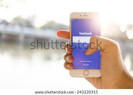 CHIANG MAI, THAILAND - JANUARY 04, 2015: A man trying to log in Facebook application using Apple iPhone 6. Facebook is largest and most popular social networking site in the world.