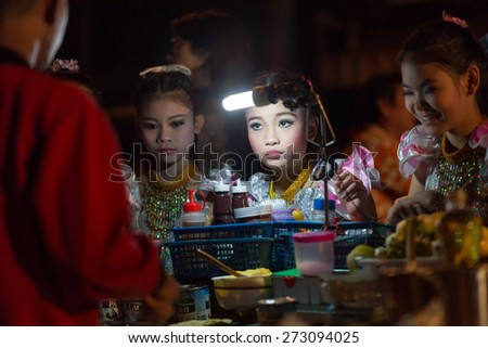 CHIANG MAI,THAILAND,JANUARY 04,2015: A Thai traditional dancer little girl is ordering a banana pancake to the street seller during the saturday night market in Chiang Mai,Thailand. - stock photo