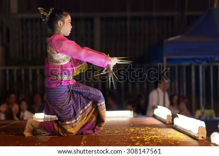 CHIANG MAI, THAILAND, JANUARY 04, 2015: A woman is performing a free Thai traditional dance in the street during the weekly Saturday night street market in Chiang Mai, Thailand - stock photo