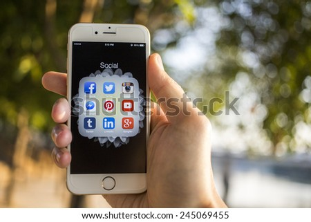 CHIANG MAI, THAILAND - JANUARY 04, 2015: All of popular social media icons on smartphone device screen with hand holding on Apple iPhone 6. - stock photo