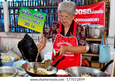 Chiang Mai, Thailand - January 6, 2013:  Woman cooking Pad Thai omelet on a wok at her sidewalk food stand