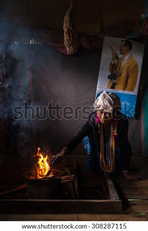 CHIANG MAI, THAILAND - JUL 25 : Karen hill tribe in her house with traditional clothes and dramatic light on July 25, 2015 in Chiang Mai, Thailand. - stock photo