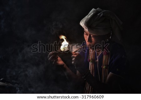 CHIANG MAI, THAILAND - JUL 25 : Karen hill tribe is smoking tobacco pipe with traditional clothes and dramatic light  in Chiang Mai, Thailand. - stock photo