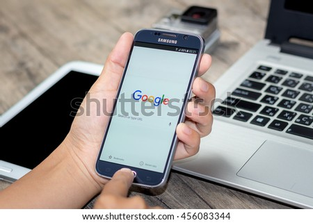 CHIANG MAI,THAILAND - JULY 21, 2016 : Asian Woman holding Samsung Galaxy S6 with google search app on the screen on Wood desk office. Top view of Business workplace.