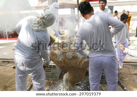 Chiang Mai, Thailand -  July 8, 2015: The man is pouring melting metal in furnace for casting buddha statue in Suntidham temple on July 8, 20.15 in Chiang Mai, Thailand. - stock photo