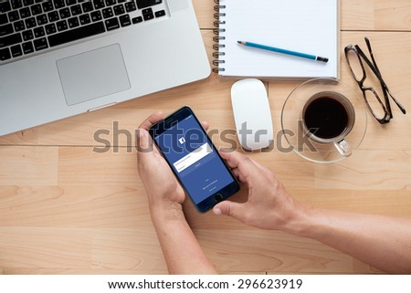 CHIANG MAI ,THAILAND - JULY 15, 2015: Young man touch Facebook icons on Apple iPhone 6 plus. Facebook is largest and most popular social networking site in the world. - stock photo