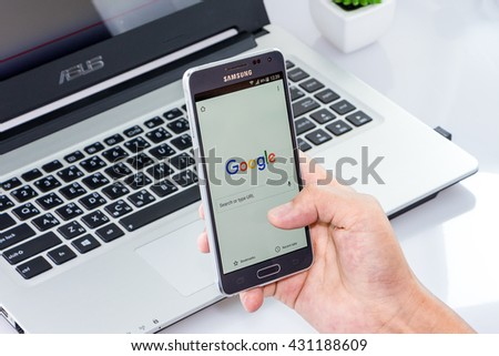 CHIANG MAI,THAILAND - JUN 4, 2016 : Woman holding Samsung galaxy Alpha with google search app on the screen on white desk office. Top view of Business workplace. - stock photo