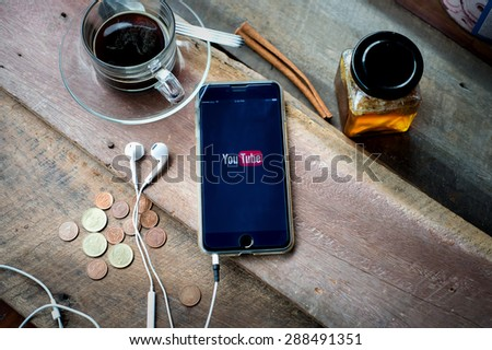 CHIANG MAI,THAILAND - JUNE 18, 2015: Brand new Apple iPhone 6 plus with YouTube app on the screen lying on old wood desk with headphones. YouTube is the popular online video sharing website - stock photo