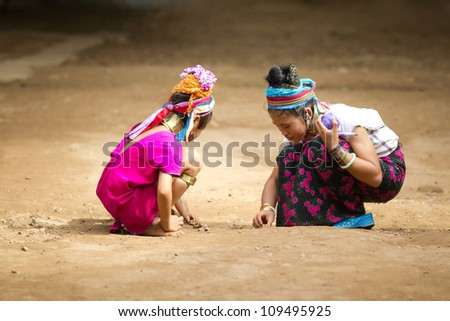 CHIANG MAI, THAILAND - JUNE 13: Unidentified Karen tribe children pose for the camera in Chiang Mai on June 13, 2012. The Karen people wear brass rings from as young as five years old. - stock photo