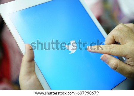 CHIANG MAI,THAILAND - March 25,2017: Close up female holding tablet computer On Hand And Start Using Twitter Application.