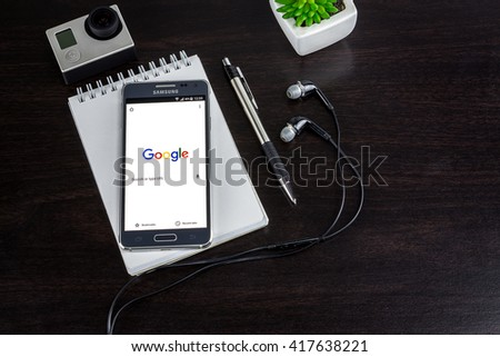 CHIANG MAI,THAILAND - MAY 09, 2016 : Samsung galaxy Alpha with google search app on the screen lying on wood desk office. Top view of Business workplace. - stock photo