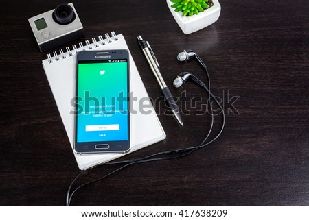 CHIANG MAI,THAILAND - MAY 09, 2016 : Samsung galaxy Alpha with twitter app on the screen lying on wood desk office. Top view of Business workplace.