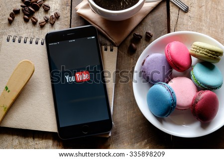 CHIANG MAI,THAILAND - NOV, 06,2015: Brand new Apple iPhone 6 plus with YouTube app on the screen lying on old wood desk with headphones. YouTube is the popular online video sharing website  - stock photo