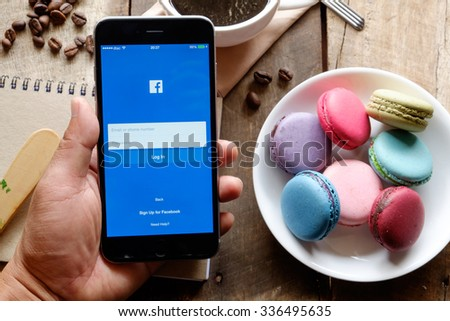 CHIANG MAI ,THAILAND - NOV 08, 2015:Young man touch Facebook icons on Apple iPhone 6 plus. Facebook is largest and most popular social networking site in the world. - stock photo