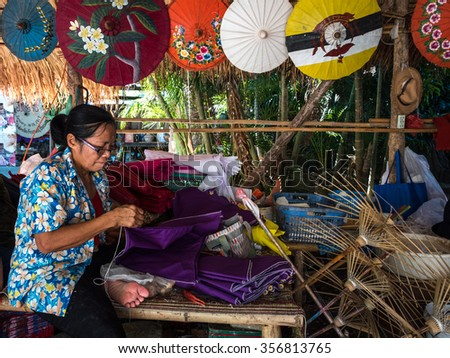 CHIANG MAI, THAILAND - NOVEMBER 22, 2015: An unidentified woman works on an umbrella in parasol factory in Chiang Mai, Thailand. This is a traditional craft that attracts local and foreign visitors. - stock photo