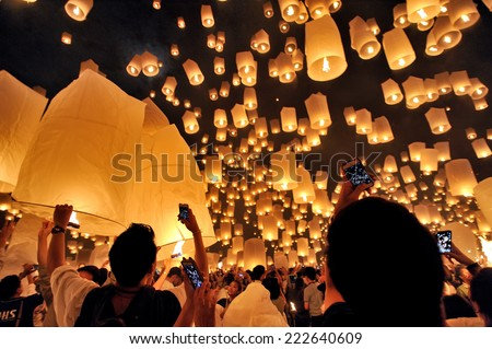 CHIANG MAI THAILAND-NOVEMBER 16 : Loy Krathong festival. Unidentified men and women lights floating balloon made of paper annually at the Sansai. on Nov. 16,2013 in Chiang Mai, Thailand. - stock photo