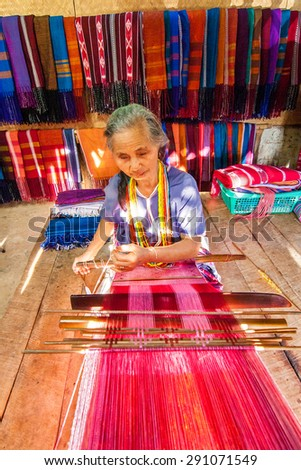 CHIANG MAI, THAILAND - NOVEMBER 18 : Unidentified tribalthai woman weaving traditional cotton woven  on Nov 18, 2010 in Chiang Mai, Thailand.