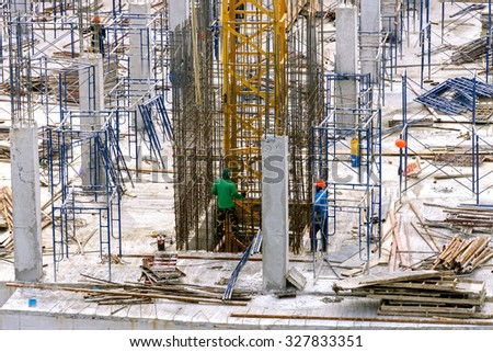 CHIANG MAI,THAILAND - OCT 10 : Workers work on the new under construction building and construction tower canes on October 10, 2015 in Chiang Mai, Thailand.