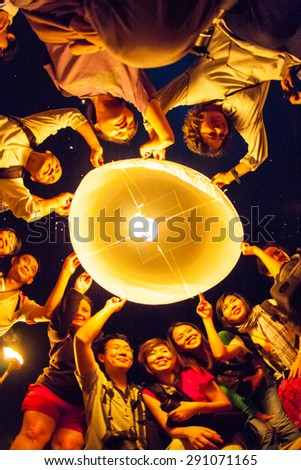 CHIANG MAI, THAILAND - OCTOBER 20, 2010: Group of Thai people launch a sky lantern on the night of the annual festival known as Yee Peng (Yi Peng). - stock photo