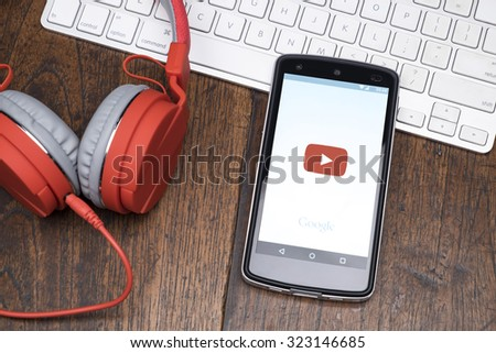 CHIANG MAI, THAILAND -October 2, 2015:LG Nexus 5 open YouTube app on the screen lying on desk with headphones. YouTube is the popular online video-sharing website. - stock photo