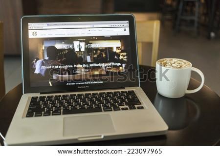 CHIANG MAI, THAILAND - OCTOBER 02, 2014: Starbucks coffee caramel latte and Apple laptop open Starbucks website on monitor. - stock photo
