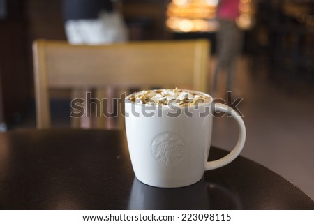 CHIANG MAI, THAILAND - OCTOBER 02, 2014: Starbucks coffee caramel latte white mug in Starbucks Cafe Chiang Mai Thailand. Starbucks is the largest coffeehouse company in the world. - stock photo
