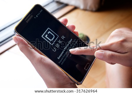 CHIANG MAI,THAILAND - SEP 16,2015 : A woman hand holding Uber app showing on Samsung note 3,Uber is smartphone app-based transportation network.