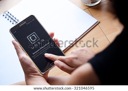CHIANG MAI,THAILAND - SEP 16,2015 : A woman hand holding Uber app showing on Samsung note 3,Uber is smartphone app-based transportation network. - stock photo