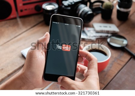 CHIANG MAI,THAILAND - SEP 29, 2015: Brand new Apple iPhone 6 plus with YouTube app on the screen lying on old wood desk with headphones. YouTube is the popular online video sharing website  - stock photo
