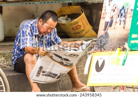 CHIANG MAI , THAILAND - SEPTEMBER 23 : An unidentified man read a newspaper on a sidewalk on September 23 , 2014 in Chiang Mai , Thailand . - stock photo