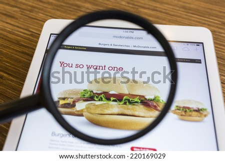 CHIANG MAI, THAILAND - SEPTEMBER 17, 2014: Close up of McDonald's homepage on Apple iPad Air through a magnifying glass on wood table. - stock photo